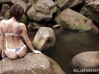 This sexy Japanese couple have found a secluded, rocky area, where they can get naughty with each other. The horny girl is wearing a bikini and she ge