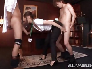 This salary woman is on her knees and in each hand she has the cock of one of her coworkers. She strokes and sucks and then, she bends over to get pou